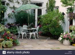 White Wrought Iron Patio Furniture by Green Umbrella Above White Wrought Iron Table And Chairs On Patio