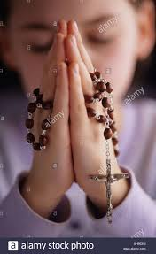 in prayer holding rosary with crucifix showing up