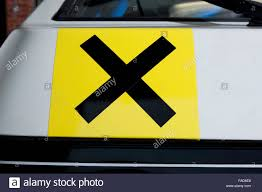 novice sticker on a car at a race track black x on yellow square