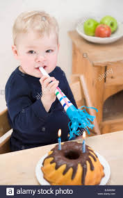 small boy with birthday cake gugelhupf and horn stock photo