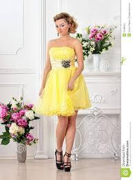 beautiful woman in yellow dress in luxury studio stock