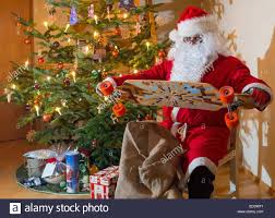 illustration santa claus sits next to a christmas tree on