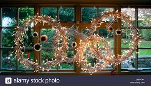 christmas lights and baubles in the form of a wreath in window at