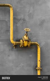 old gas gate of yellow colour is on a pipe and blocks a pipe the