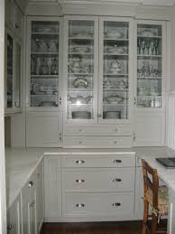 l shaped white stained wooden kitchen cabinet with glass door