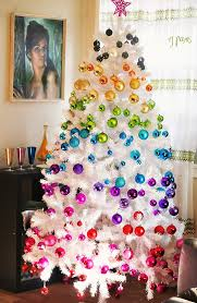 small white christmas tree tree with multicolored ornaments in diagonal stripes ombré