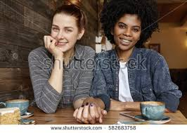Interacial Lesbians - happy interracial lesbian female couple relaxing stock photo
