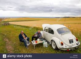 yellow volkswagen beetle royalty free two dutch tourists have a picnic beside their vw beetle in a field