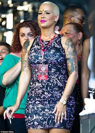 parrot eye amber rose gets an inverted tattoo cross design on
