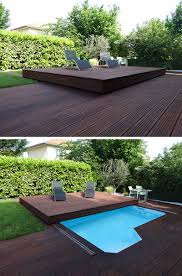 this raised wooden deck in the backyard is actually a pool cover