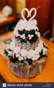 cute wedding cake with green leaves white roses and two swans on