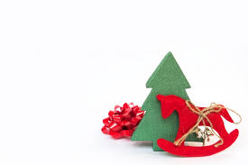 Christmas Decorations On White Background by Tie With A Christmas Tree And A Toy Horse On A White Background
