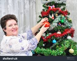 what to get an elderly woman for christmas elderly woman decorates christmas tree stock photo 65978419