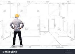 engineering person standing near house blueprints stock
