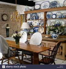 dresser in dining room old stock photos dresser in dining room simple wood table and chairs with white slip covers in cottage dining room with collection of