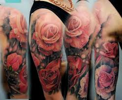 upper arm tattoo of photo realistic red pink and orange roses