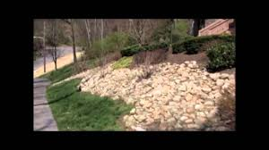 video showing a slope landscaped with natural stone and shrubs