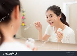 pretty sweet woman in bathroom at home looking at mirror
