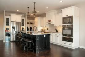 white kitchen with black island stacked moulding glazed kitchen cabinets white kitchen