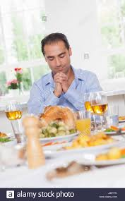 saying grace before thanksgiving dinner stock photo royalty