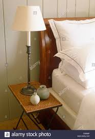 lamp on wicker bedside table next to sleigh bed with crisp white