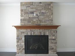 brown wooden mantel shelf over black fire box of grey stone