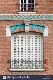 window with white wooden shutters blue painted ornamental arch