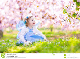 beautiful toddler in fairy costume in fruit garden stock