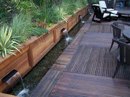 long brown wooden water fountains with small pond and green plant