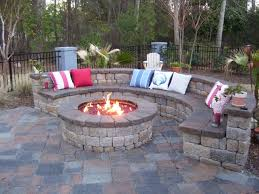 Winter Patio Plants by Exterior Fire Pit Near Stone Bench Beyond Black Garden Fences Of
