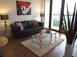 middle table living room love seat sofs with cushions on the middle of glass table and ls