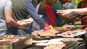 sit around grill table close up of man food grilling on barbecue while women sit at