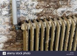old radiator with paint peeling off mounted on damp cellar wall