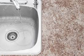 water running from kitchen faucet clean new sink and countertop