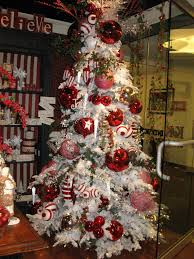 flocked tree with oversized ornaments deck the halls