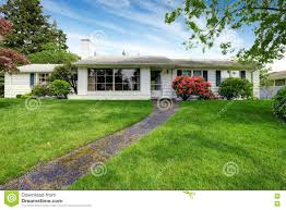 Rambler House by American White Rambler With Green Grass And Flower Bed Stock