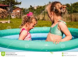 kid girls swimming in the pool in backyard stock photo image