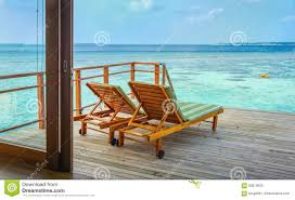 two wooden lounge chairs on the deck of water bungalow suite
