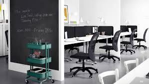 bureaux blancs bureau partagé avec chaises noires et séparateurs noirs entre les