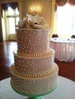 gold and cream wedding cake with gold bows holiday market wedding