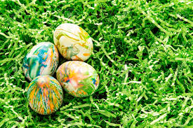 green paper easter grass tie dyed easter eggs nestled in green colored paper grass stock