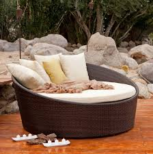 round resin wicker outdoor chaise lounge with pillows and rock