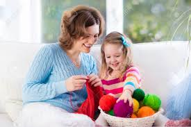 mother and daughter knitting woolen scarf mom teaching child
