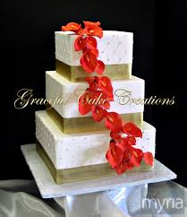square ivory wedding cake with gold ribbon and burnt orange calla