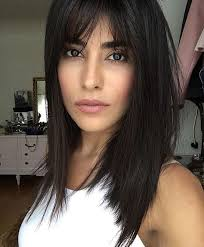 hairstyles for foreheads that stick out on a woman stick straight black hair with long parted bangs long bangs