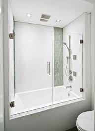 frameless tub shower with glass doors having grey ceramic wall as