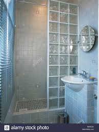modern tiled bathroom with glass brick shower wall and blue mosaic