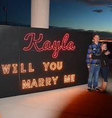 will you marry me signs in lights proposal at glittering lights on christmas eve