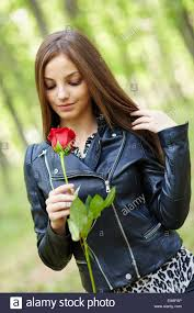beautiful teen with a red rose outdoor in the forest stock