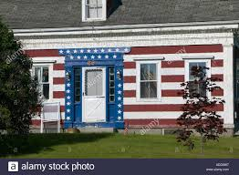 facade of old salt box style house in rural maine painted in red